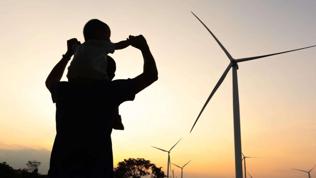 Vater mit Kind auf der Schulter vor Windrad in der Abendsonne
